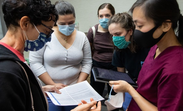 School of Public Health students meet with a professor while wearing masks as they examine data.