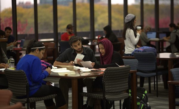UIC students sit at a table together studying in the UIC library.